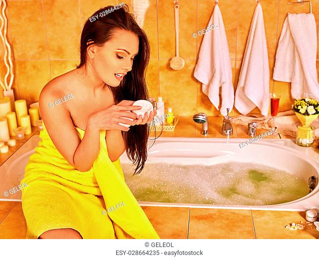 Woman applying moisturizer at bathroom. Yellow towel