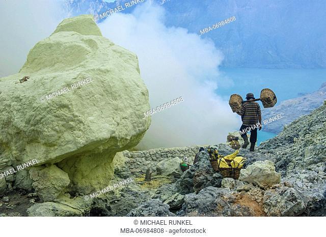 Worker walk near a huge block of Sulphur, Ijen Volcano, Java, Indonesia