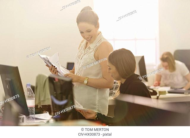Businesswomen discussing paperwork at computer in office
