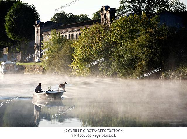 A man on a boat passes by the cognac house of Tiffon, on the banks of the Charente river, Jarnac, Charente departement, France