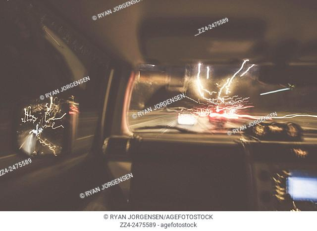 Fast pace long exposure motion blur inside a vehicle speeding along a highway in a blur of traffic light and speed. The getaway car chase