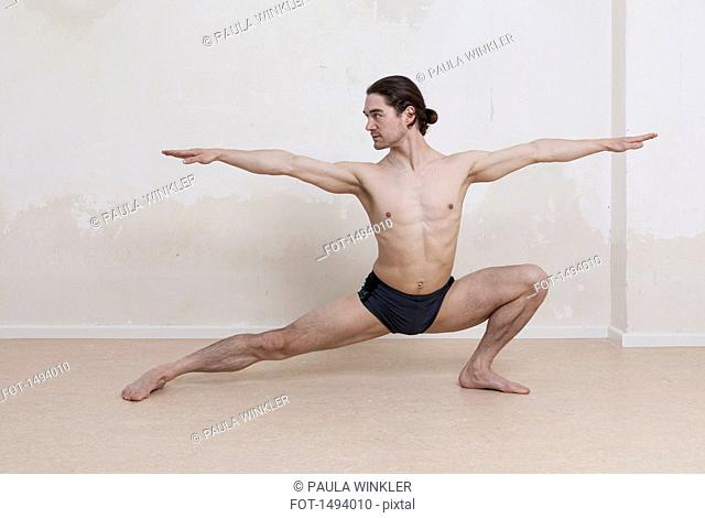Determined man practicing yoga in warrior position against white background
