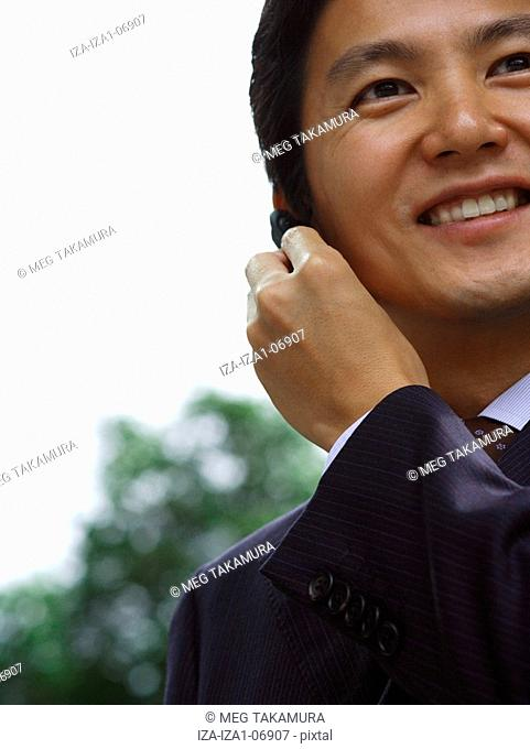 Close-up of a businessman using a bluetooth device and smiling
