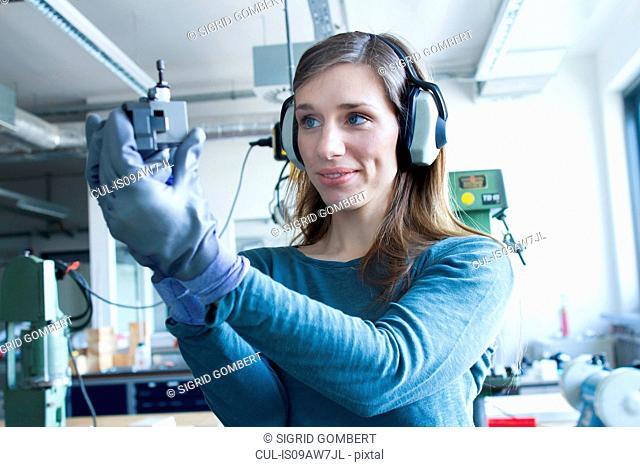 Woman in workshop wearing ear defenders operating machine smiling