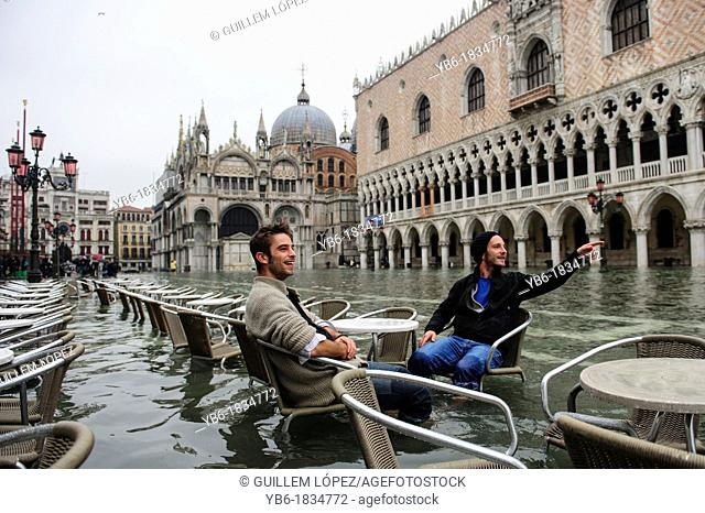 A couple of tourists sitting in one of the Cafe Terraces of the flooded St. Mark's Square, Venice, Italy