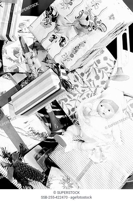 Doll lying on gift boxes