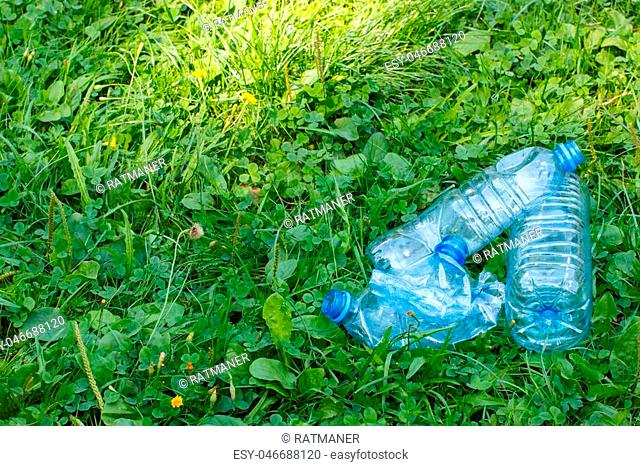 Crushed plastic bottles of mineral water on grass in sunny park, concept of environmental protection, littering of environment
