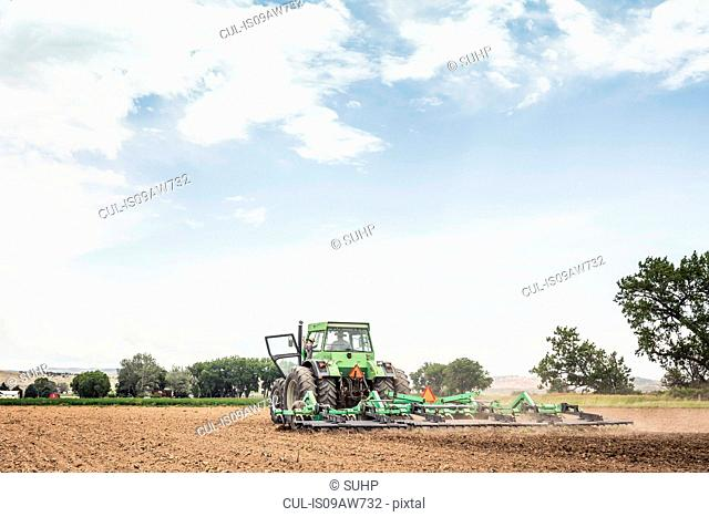 Farmer and teenage grandson waving whilst ploughing with tractor