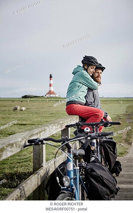 Germany, Schleswig-Holstein, Eiderstedt, couple on bicycle trip having a break near Westerheversand Lighthouse
