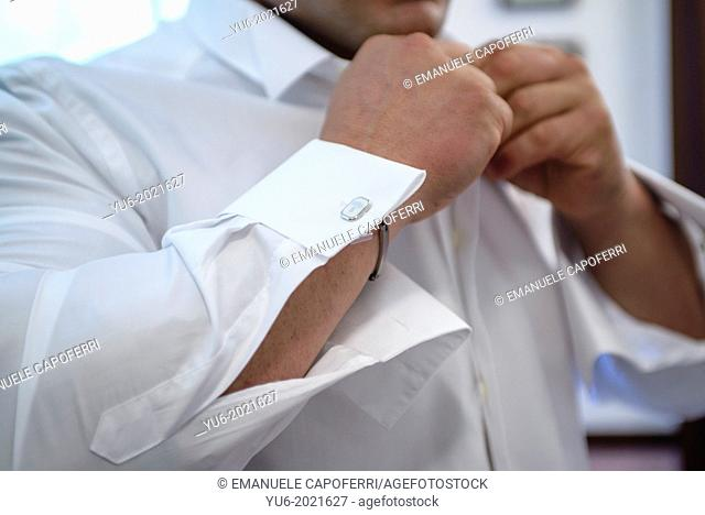 man fastens his elegant shirt