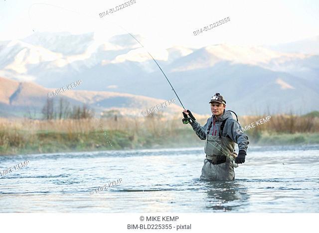 Caucasian man fly fishing in river