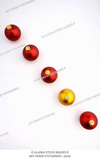 Looking down on one gold Christmas tree bulb ornament in line with four red bulbs on white background studio portrait