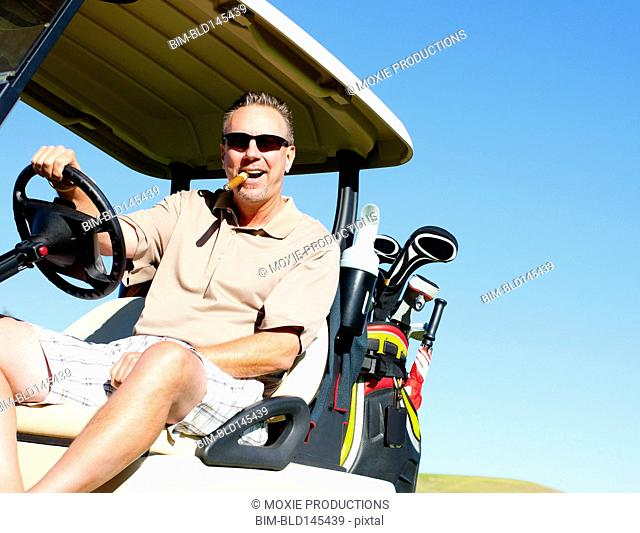 Caucasian man with cigar driving golf cart