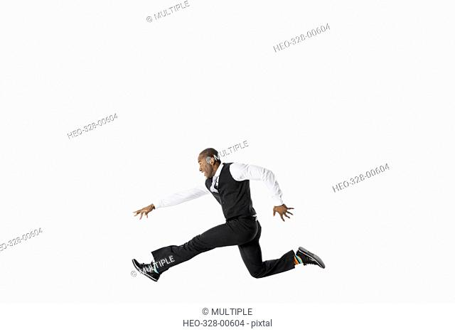 Exuberant businessman running and jumping against white background