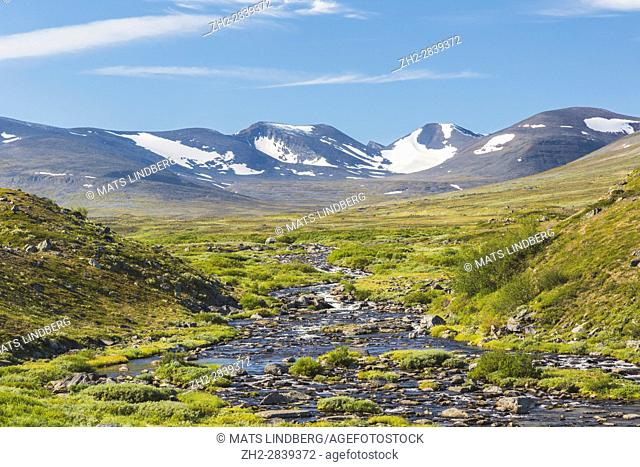 Mountain area in Swedish Lapland, creek running in to the picture and snow on the mountains in the month of august, Kiruna, Sweden