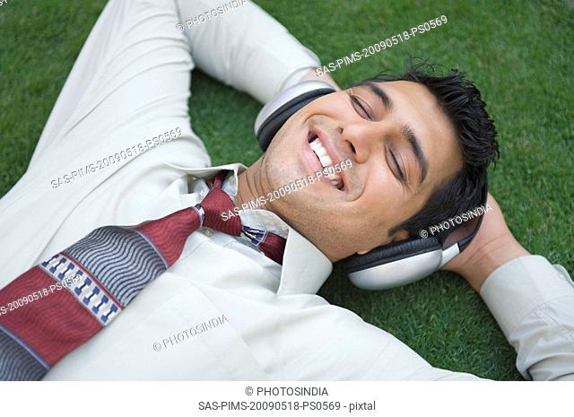 Businessman listening to music and smiling