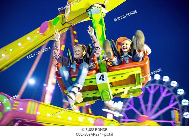 Sister and brother mid air on fairground ride at night