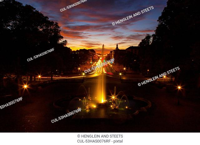 Ornate fountain with traffic at night