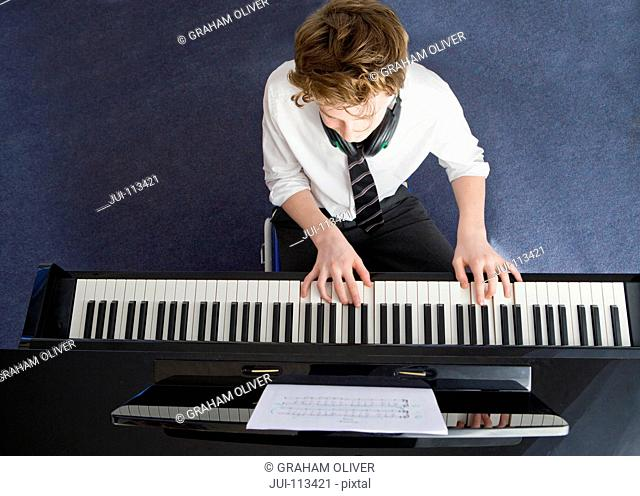 High school student playing piano in music class