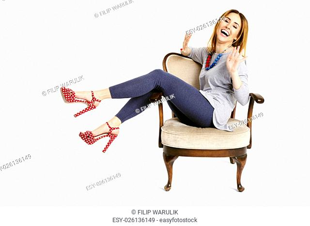 Woman sitting on a old school chair laughing and having fun