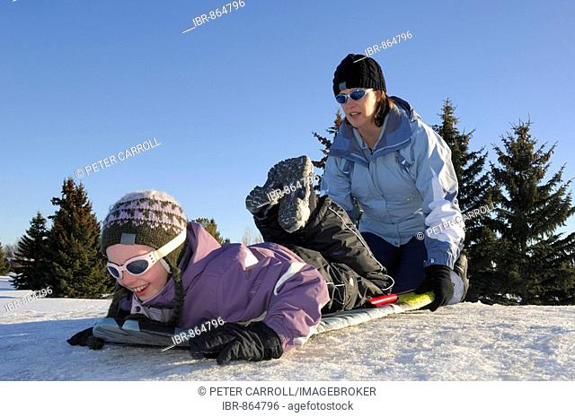 Mother preparing to give daughter a little push down a tobogganing hill