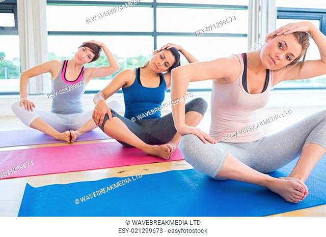 Women sitting and stretching at yoga class in fitness studio
