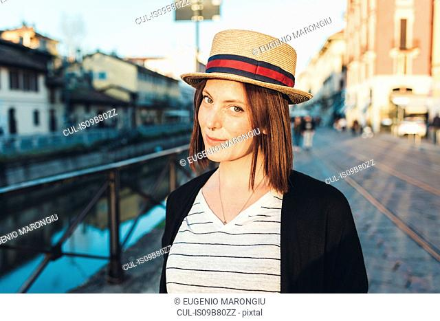 Portrait of young woman in straw boater by canal