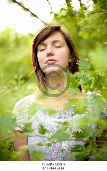 A young slim attractive girl in her late teens or early 20's, outdoors in a woodland glade  with her eyes closed, UK