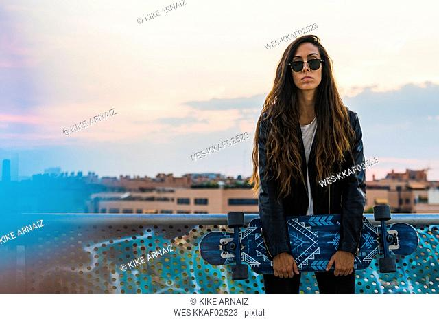 Portrait of cool young woman holding skateboard in the city