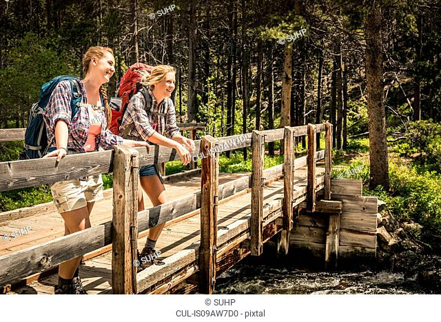 Teenage girl and young female hiker looking out from river footbridge, Red Lodge, Montana, USA