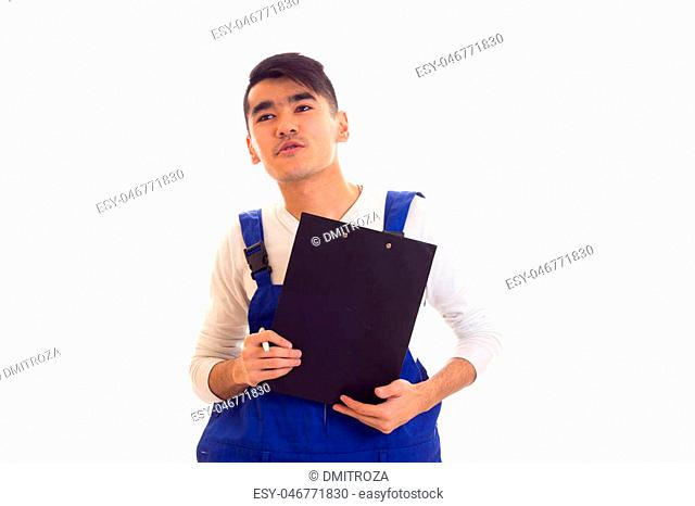 Young charming man with dark hair wearing in white shirt and blue overall holding white pen and black folder and talking on white background in studio