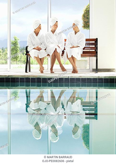 967cbd007d Women in bathrobes talking on bench poolside at spa