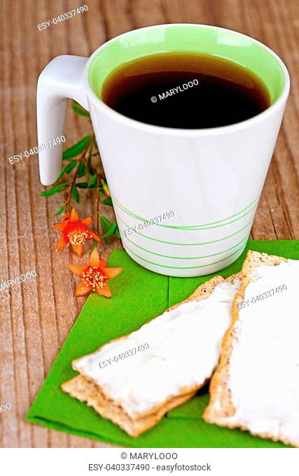 cup of tea and crackers with cream cheese closeup on wooden table