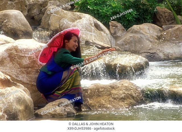 Asia, Thailand, Ayutthaya, Thai Woman Playing at Waterfall