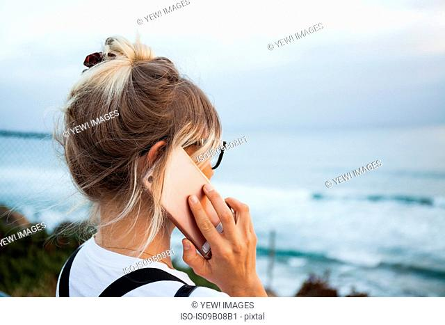 Woman by ocean making telephone call on smartphone, Encinitas, California, USA