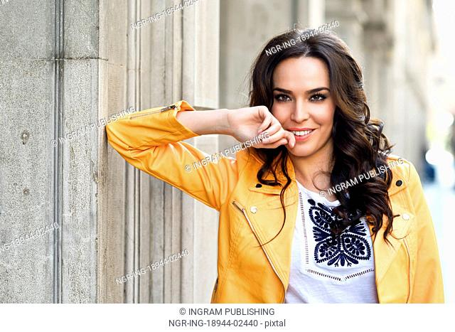 Young brunette woman, model of fashion, wearing orange modern jacket. Pretty caucasian girl with long wavy hairstyle. Thoughtful female in urban background