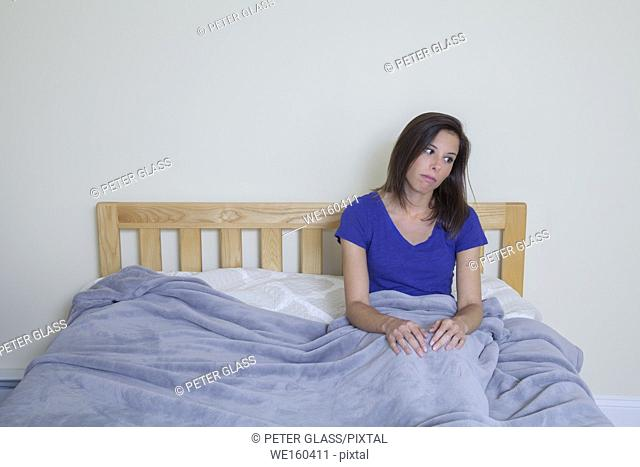 Young woman sitting on her bed, covered by a blanket