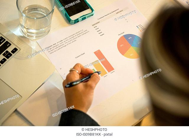 Over shoulder view of businesswoman looking at piecharts at office desk