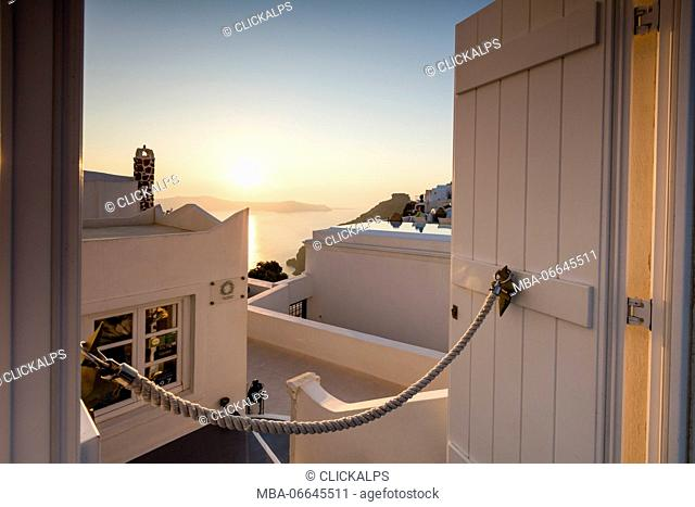 Sunset on Aegean Sea seen from a typical Greek house in the old village of Firostefani Santorini Cyclades Greece Europe