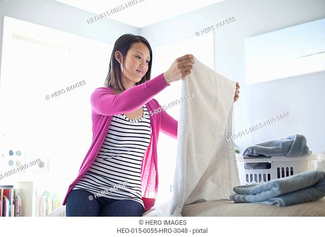 Young woman folding towel in bedroom