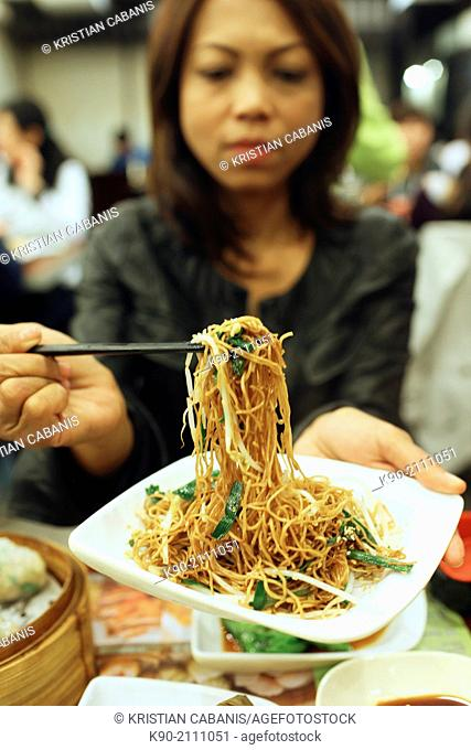 Asian woman eating chinese noodles, Kowloon, Hong Kong, China, East Asia