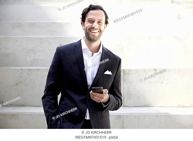 Smiling businessman with smartphone in a modern building