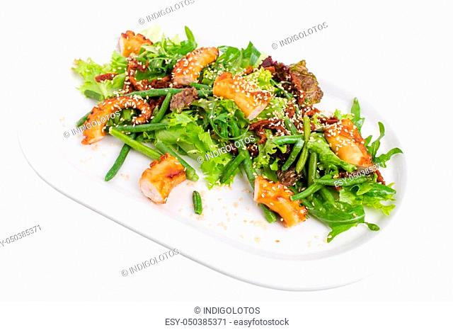 Salad with grilled octopus and dried tomatoes. Isolated on a white background