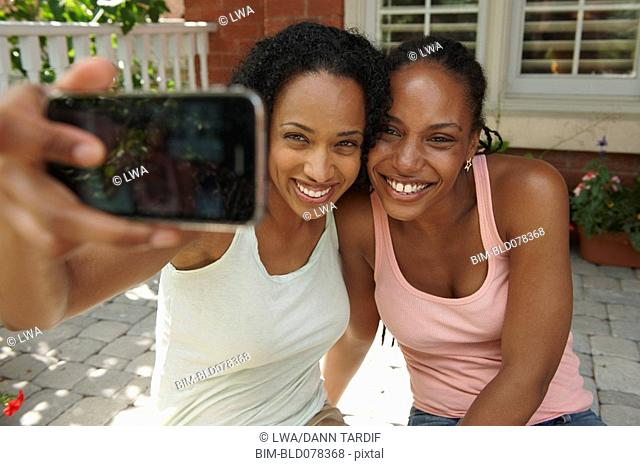 African American sisters taking self-portrait with cell phone