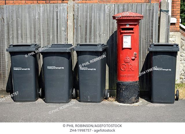 Maidstone, Kent, England. Row of household rubbish bins and red letterbox