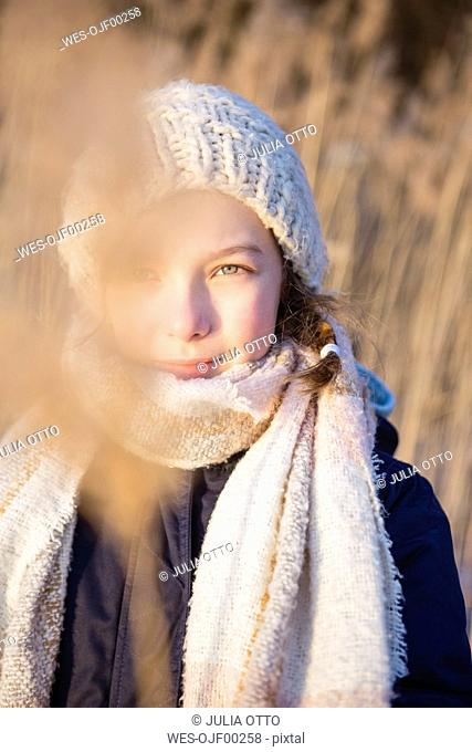 Germany, Brandenburg, Lake Straussee, portrait of a girl standing in front of reed