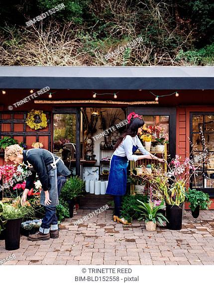 Florists arranging flowers outside shop