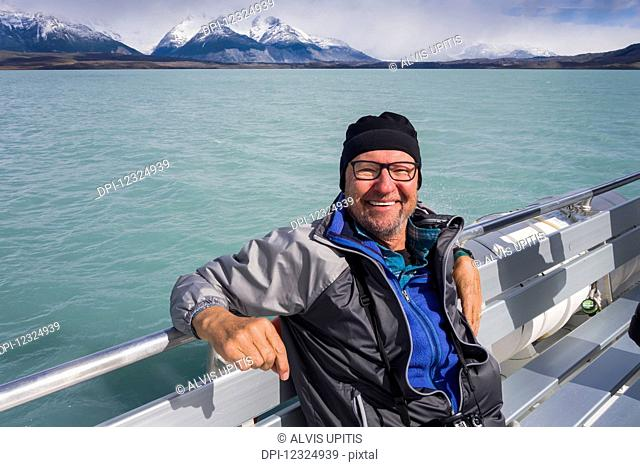 A tourist sits on a boat and poses for a picture on a cruise of Lake Argentino near El Calafate, Argentinian Patagonia; El Calafate, Santa Cruz Province