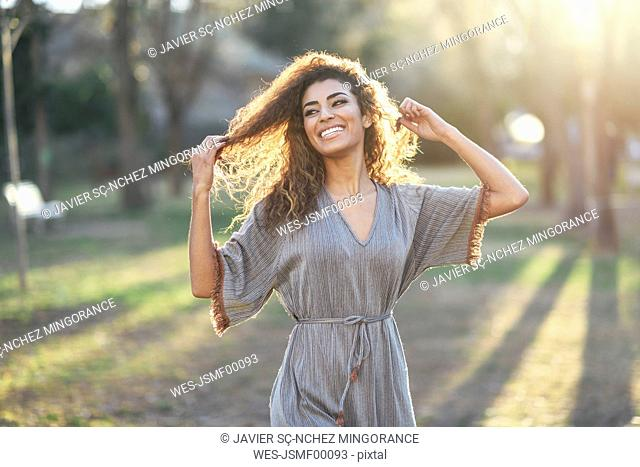 Portrait of happy young woman in a park at backlight