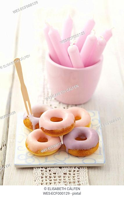 Glazed baked doughnuts on tile with candles in glass